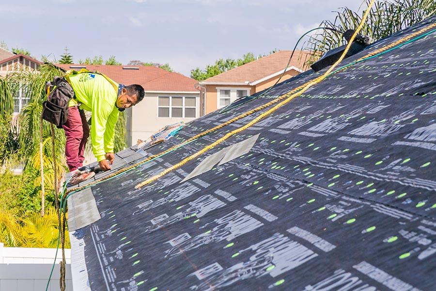 roofer installing asphalt roof