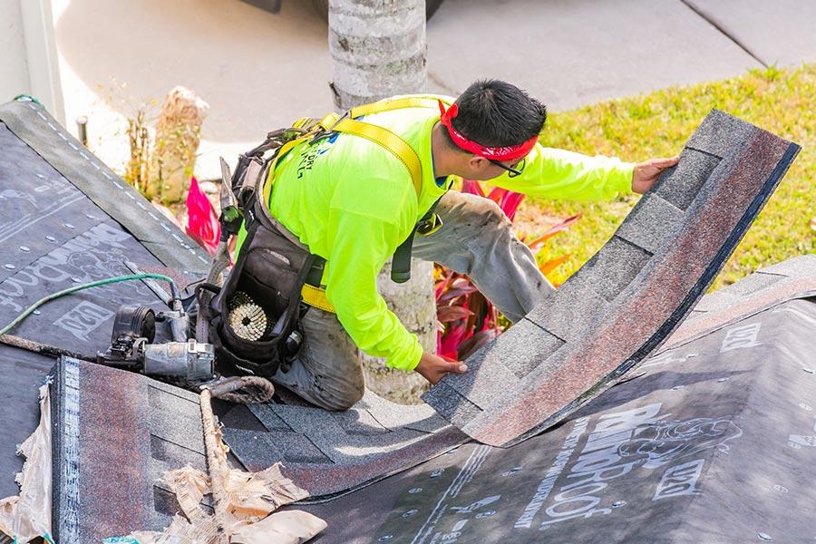 roofer with flourescent shirt installing asphalt roof